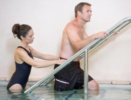 Patient and rehab therapists on the pool stairs